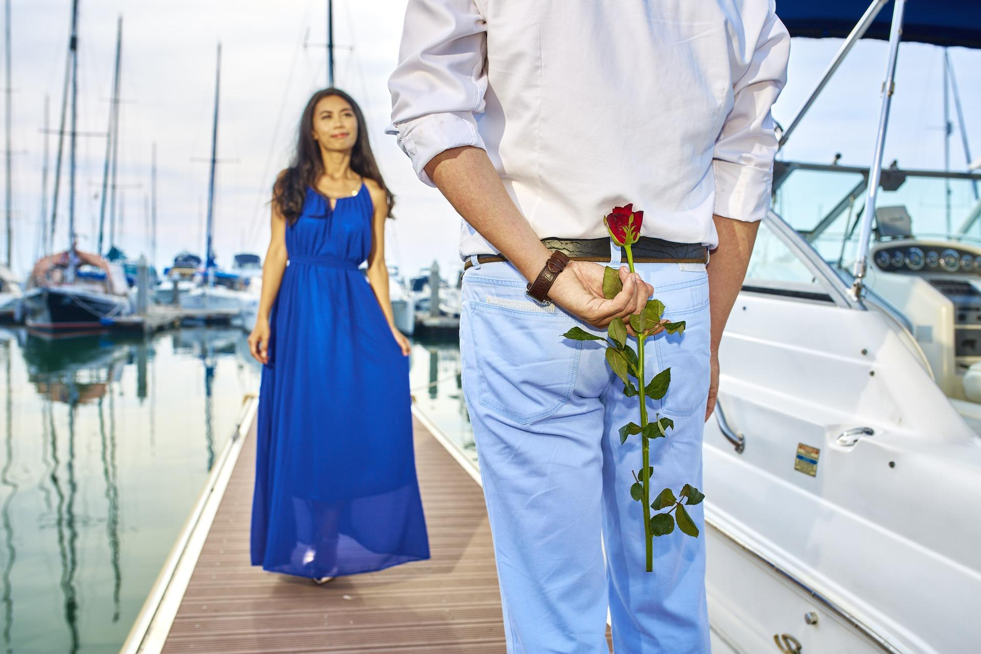 Husband surprising wife with rose and a chartered yacht