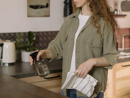 Woman spraying water and soap solution to the kitchen marble countertops in her kitchen.