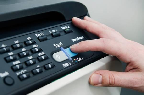 Man pushes start button of laser printer