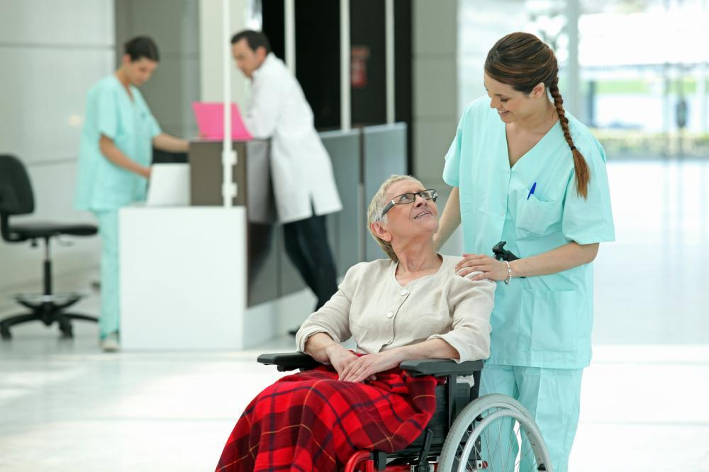 An older adult in a wheelchair with a nurse.