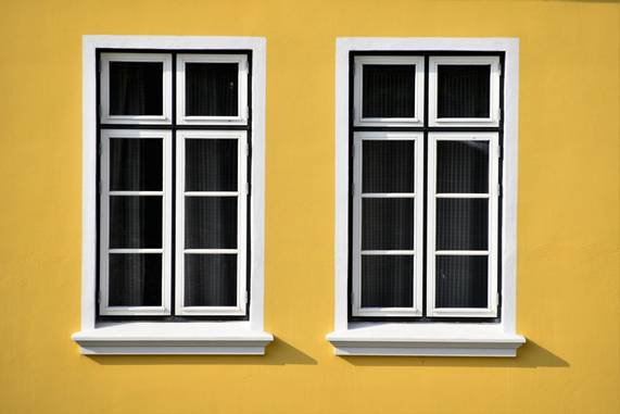 White wooden framed windows on a yellow wall