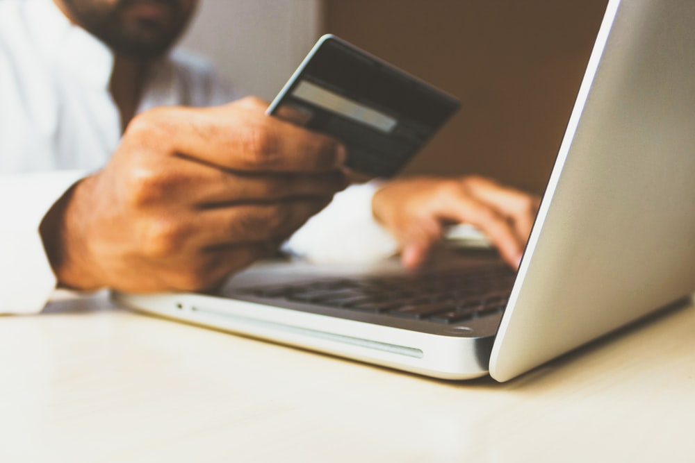 A man using his credit card to pay his bills online