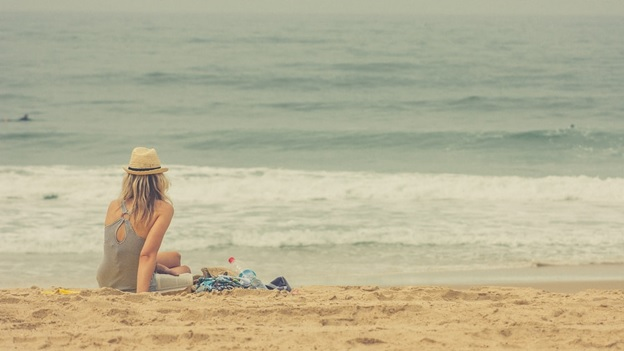 A beach lover enjoying her alone time at the beach.