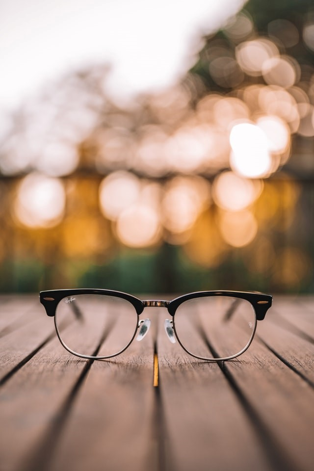 A pair of glasses on wood floor.