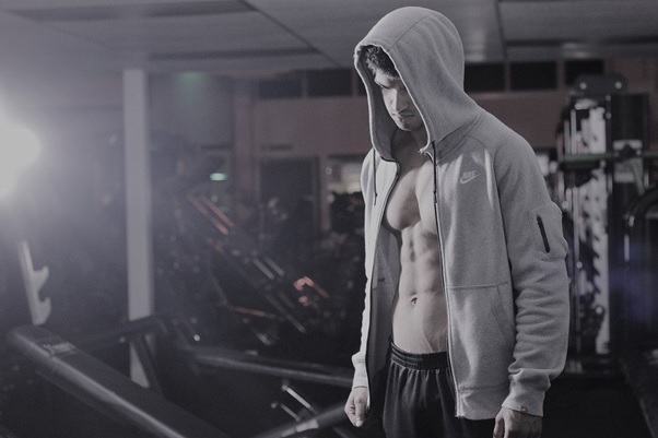 A man wearing a hoodie in a gym
