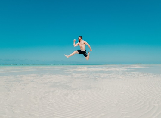 A man doing the jump pose at the beach