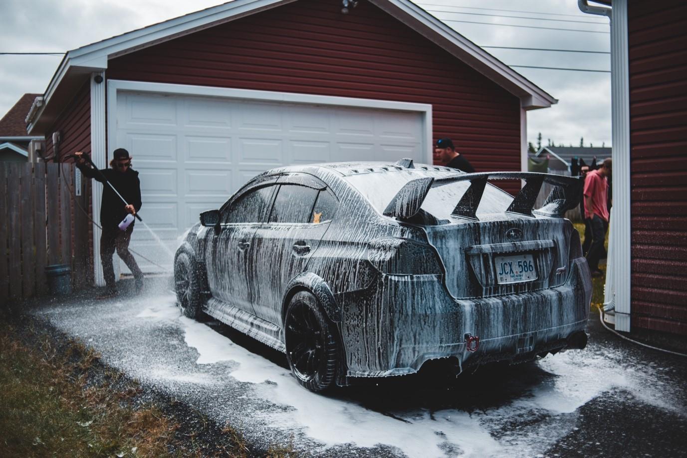 A person giving their car a power wash