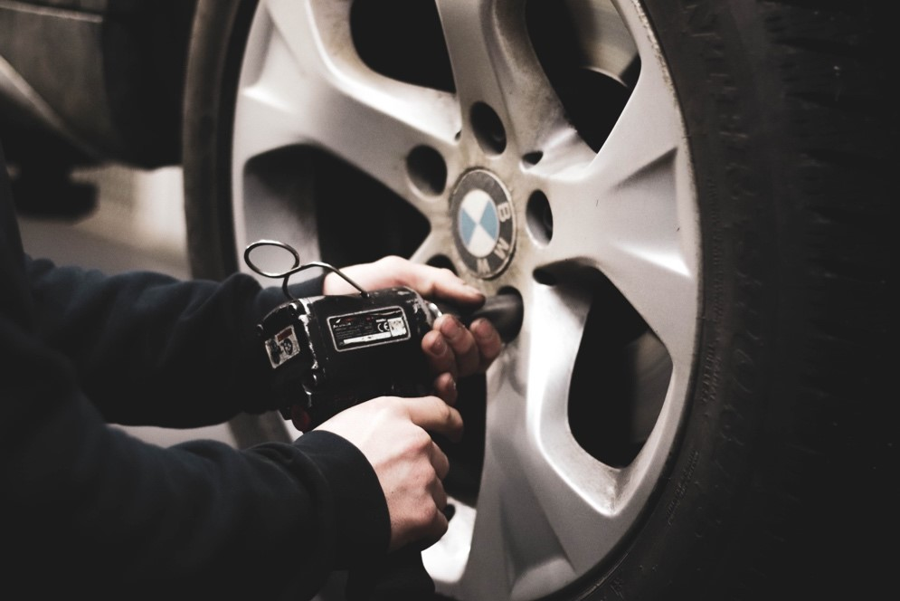 A person checking a BMW's tire