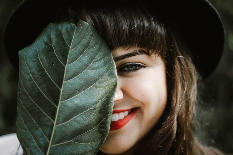 Woman smiling while covering half face from a leaf
