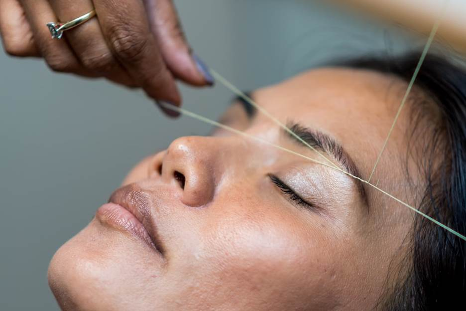 Woman getting eyebrows threading