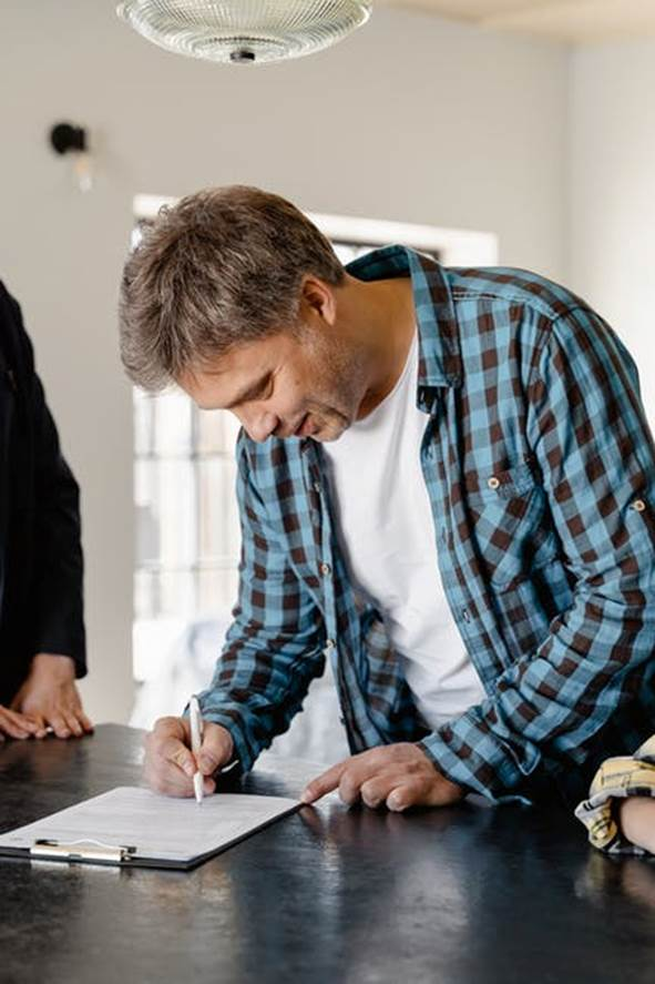 A man looks happy as he signs papers while talking to his real estate agent.