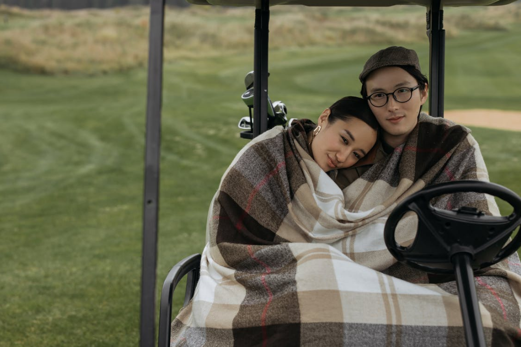 A couple is on a date and cuddling together under a blanket in a golf cart
