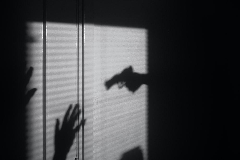 A shadow of a person pointing a gun toward a victim