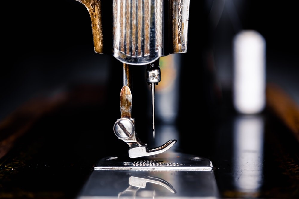 A close up of a needle attached to a sewing machine