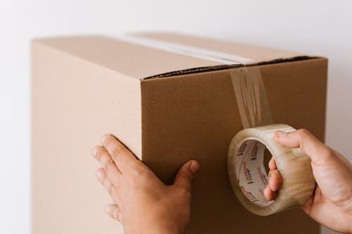 A person taping a cardboard box shut