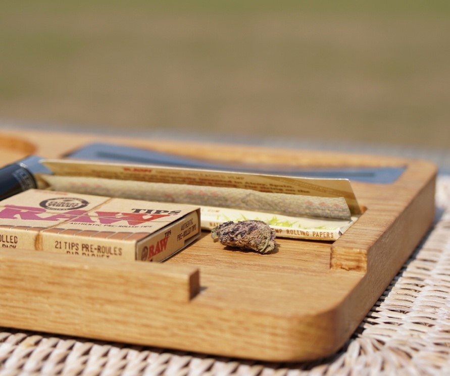 A pack of rolling paper lying on a wooden rolling tray