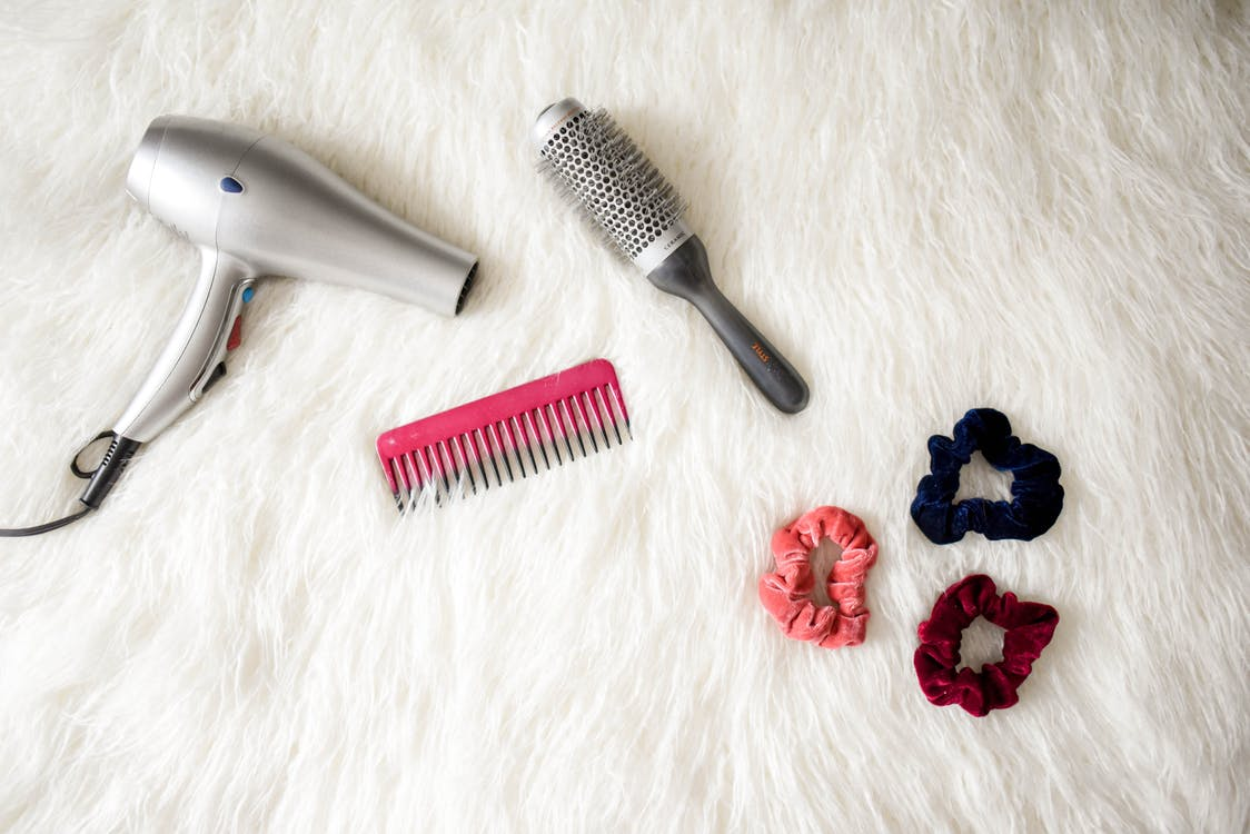 Hair styling tools including a blow dryer, scrunchies, styling brush and a comb.