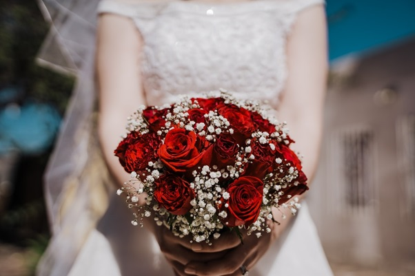 A bride holding a red roses bouquet