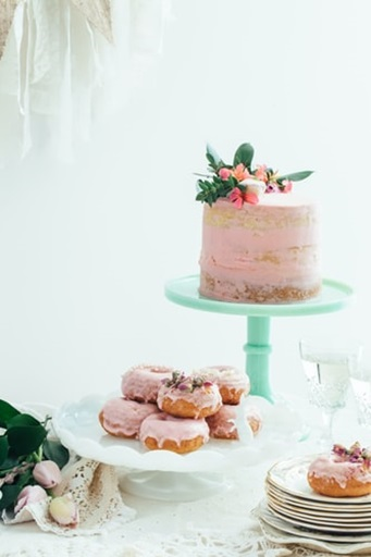 A dessert table with pink donuts and a cake, hinting at the baby's gender.