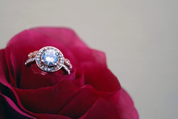 A Diamond Engagement Ring on A Red Rose