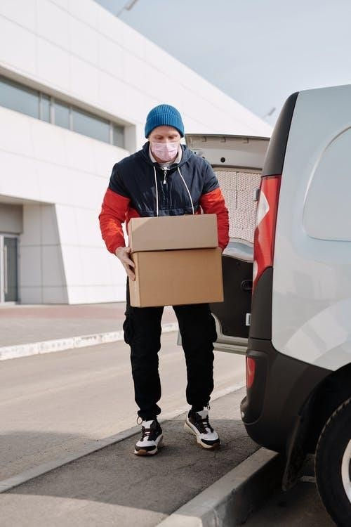 A delivery man wearing a mask and carrying boxes