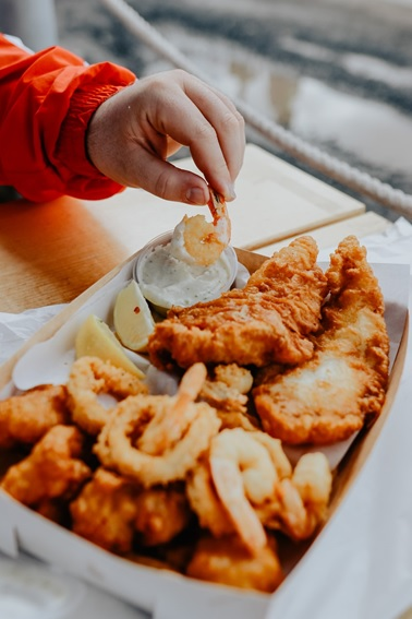 A fried seafood platter with lemon and dip.