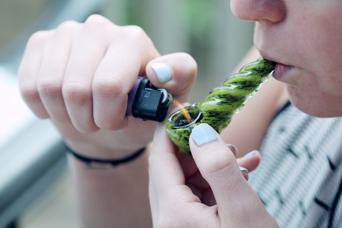 A person smoking with a green glass hand pipe