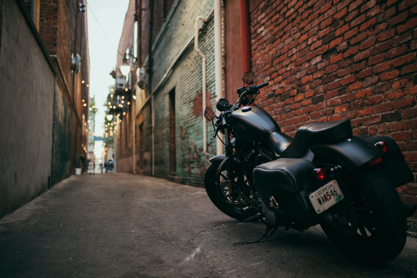 A Motorbike Parked by A Brick Wall In An Alley