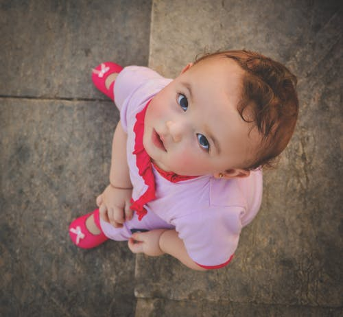 a toddler in pink shoes