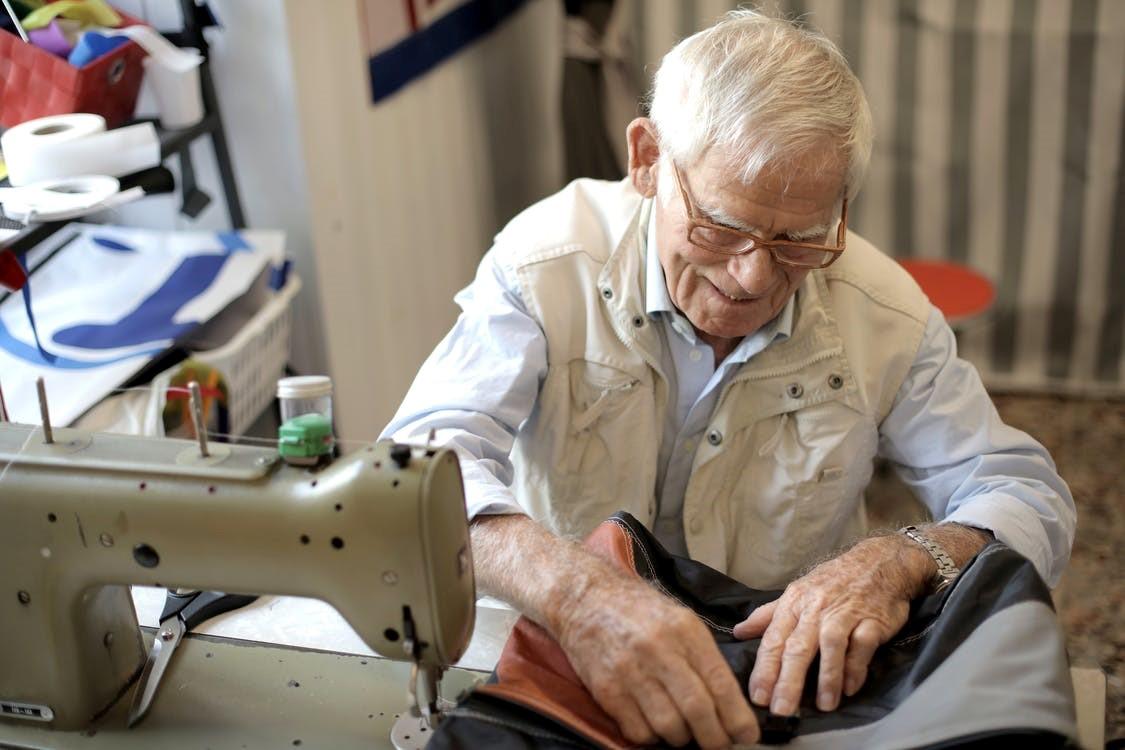 A senior citizen using a sewing machine