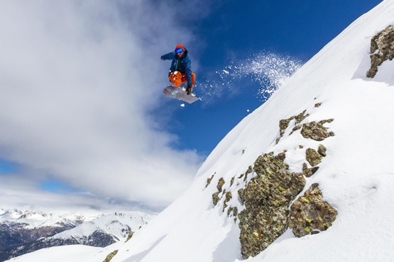A snowboarder riding a custom-made snowboard on the mountains.