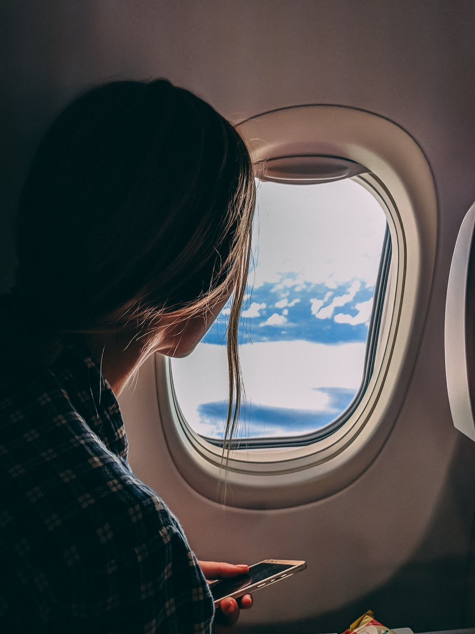A woman looking out the window in an airplane