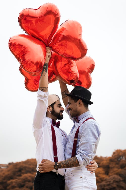 A queer couple with heart balloons