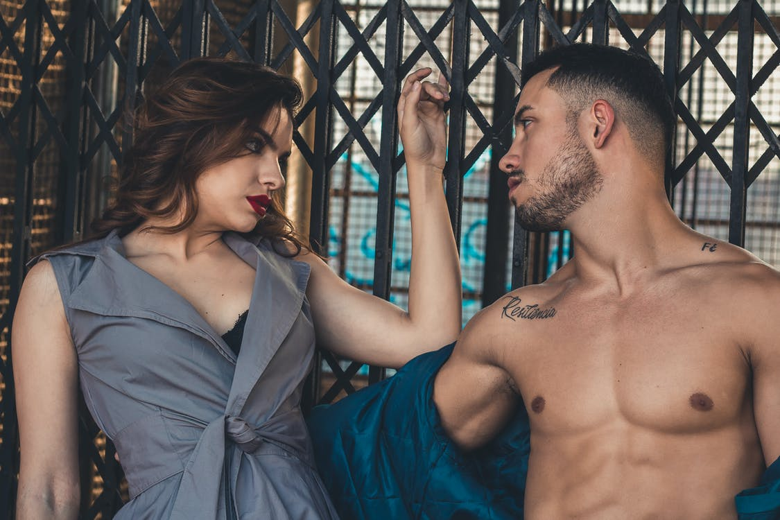 A sexy couple gazes into each other's eyes during a seductive pose.