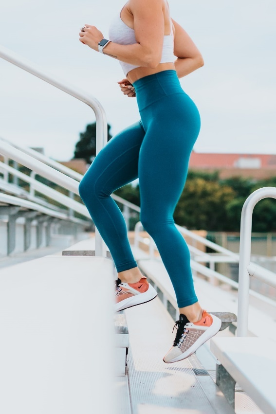 A woman jogging while wearing a fitness watch