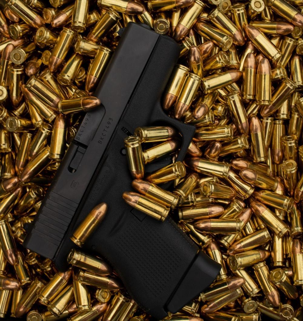 A black handgun lying on a heap of bullets
