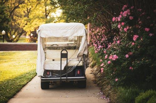 A golf cart covered by a cloth