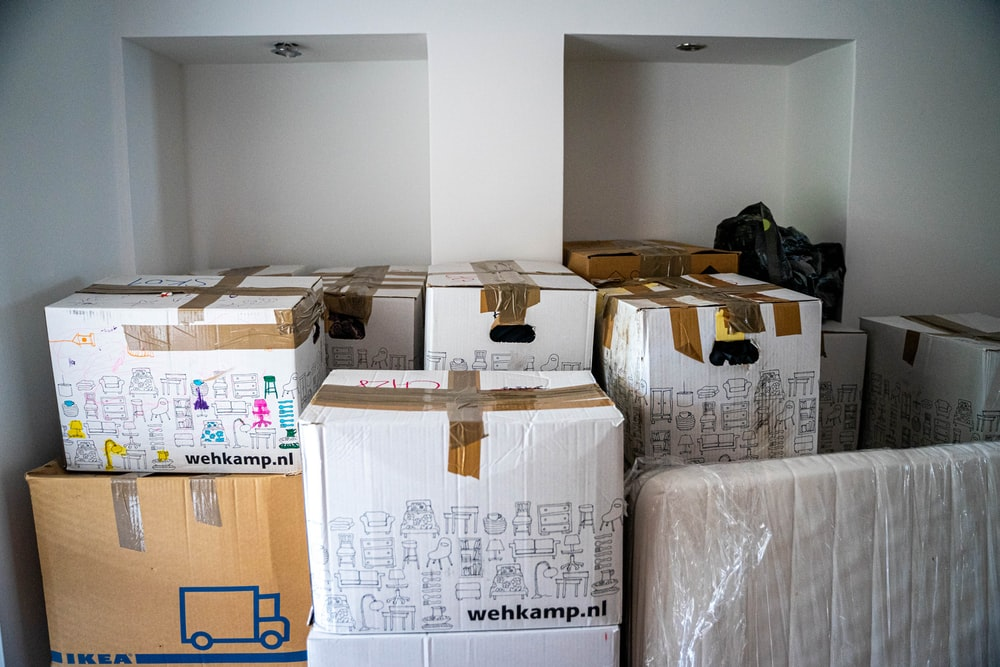 Cardboard boxes with household items, packed for moving.