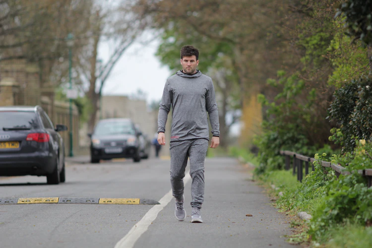 A man wearing a grey tracksuit