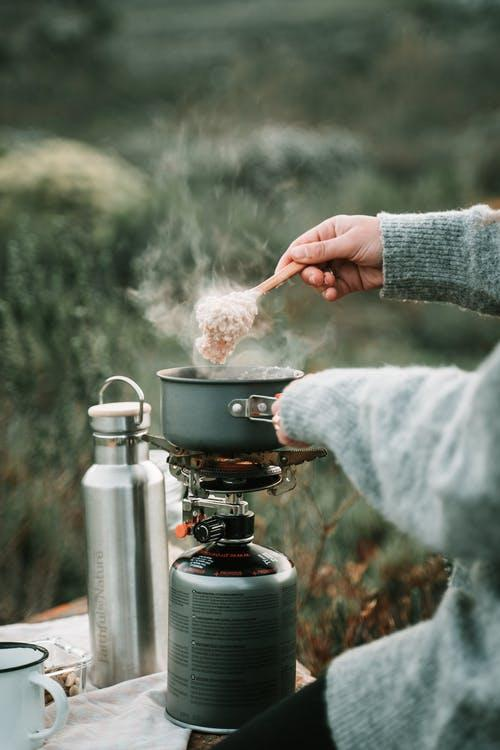 Person holding kettle on stove