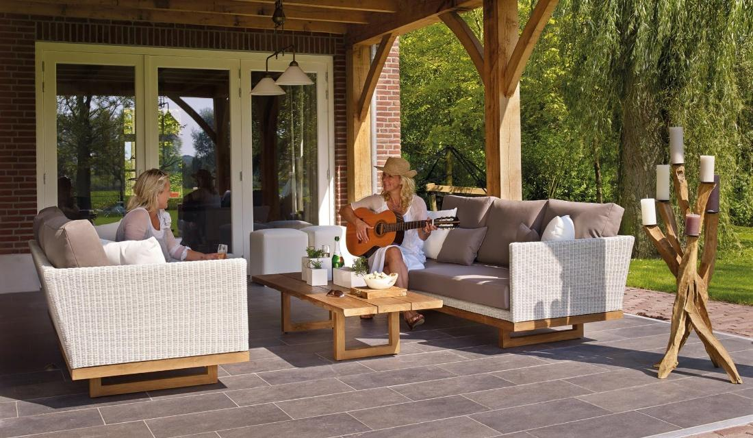 two women are sitting on sofas on a patio and playing guitar.