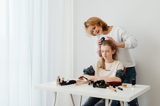 A mother brushing her daughter's hair